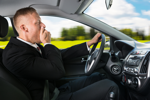 tired man in business suit yawning as he drives