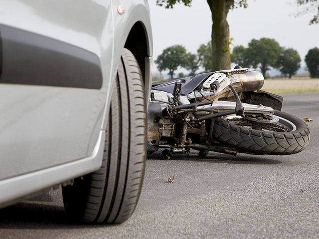 motorcycle laying on ground after accident with car