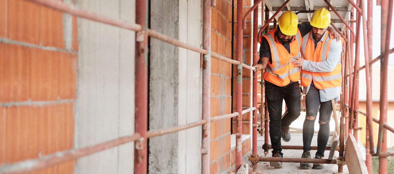 Injured construction worker being helped to walk through scaffolding by coworker
